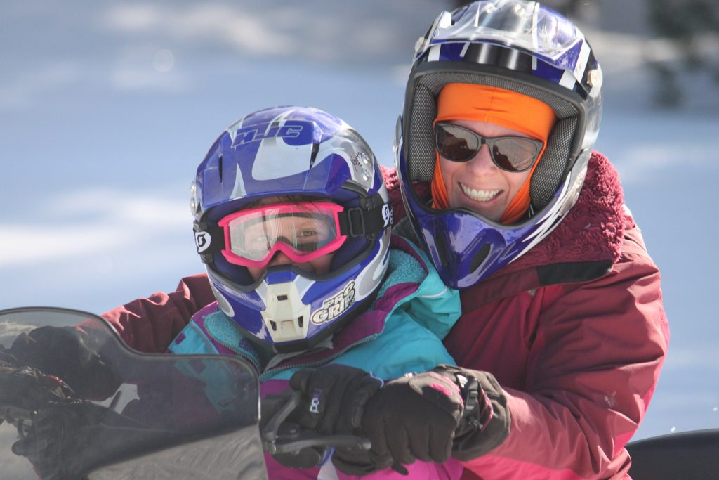 Mom and Daugher on theri Explore! Touring COmpany snowmobile